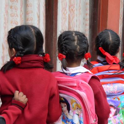 Children line up with their backpacks outside their classroom in Nepal.